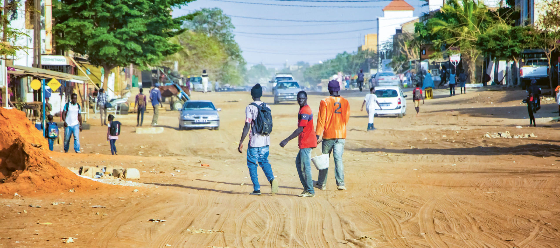 Mbour, SENEGAL – APR 26, 2019: Unidentified Senegalese men are walking down a dusty road in the middle of the city. There's a car on the sand. It is town in Africa